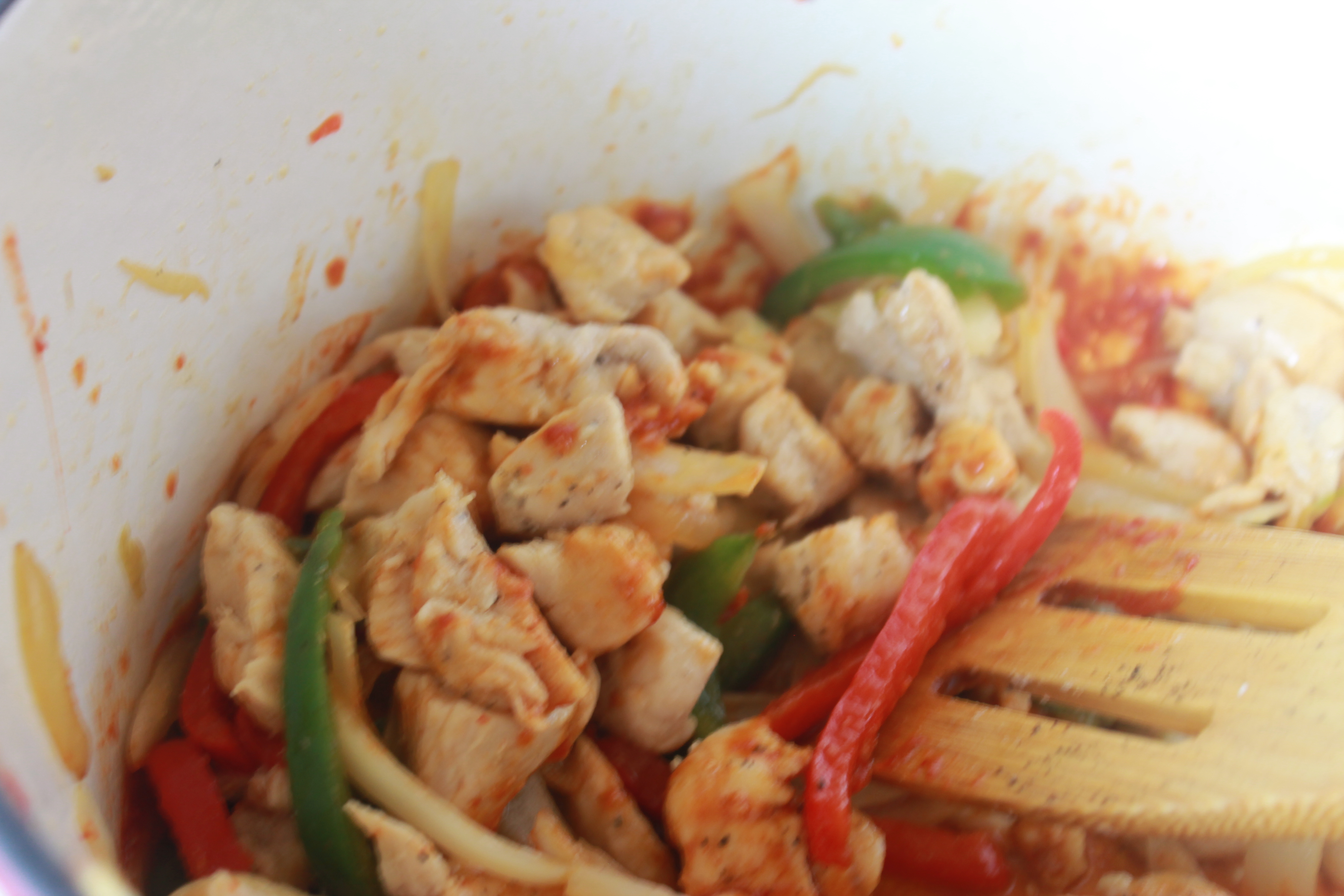 chicken, peppers, and red curry in pot cooking with wooden spatula stirring
